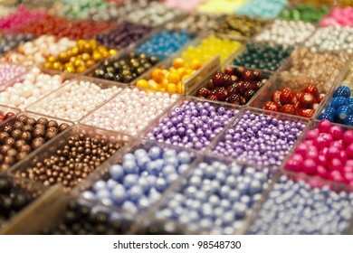 multi-colored beads in a box on a shelf in the market