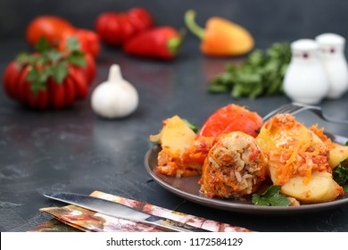 Multicolored bell pepper stuffed with meat, rice and tomato sauce. It is located in a plate on a dark background. In the photo there are fresh tomatoes, peppers, garlic and a bunch of parsley.