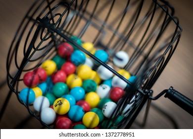 Multi-colored bingo balls in cage sitting on a desk.