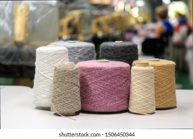 Multicolored bobbins of wool yarn for hand and machine knitting. Selective focus.