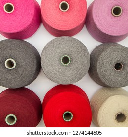 multi-colored bobbins of yarn on a white background. View from above
