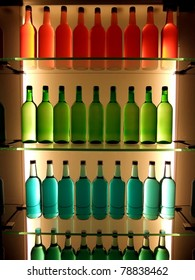 Multi-colored bottles on glass shelves