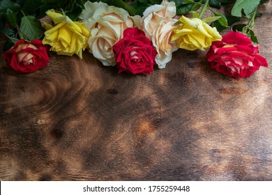 Multicolored bouquet of fresh roses on a wooden background.
