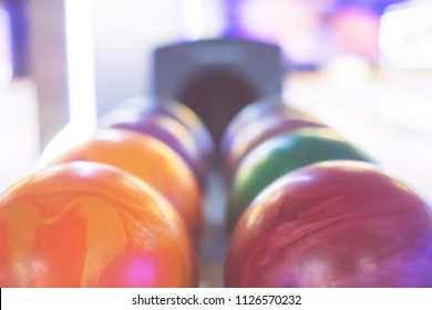 Multicolored bowling balls arranged in a row. Vivid colors. Summer day,