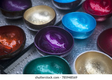 the Multicolored bowls of coconut shell with rain drops