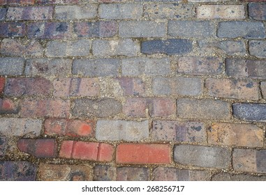 Multicolored brick cobblestones abstract background texture with rich vibrant shades of gray red orange blue and pink. Taken in Victorian Village, Columbus, Ohio USA
