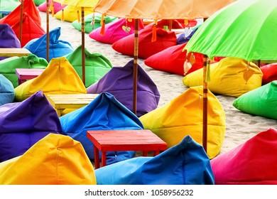 Multicolored bright beach umbrellas, ottomans and tables in the beach cafe. Summer multicolored background. Bali, Indonesia.