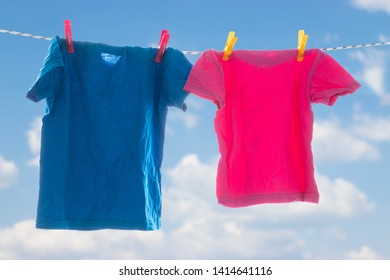 Multicolored bright clothes are drying on a rope against the blue sky with clouds