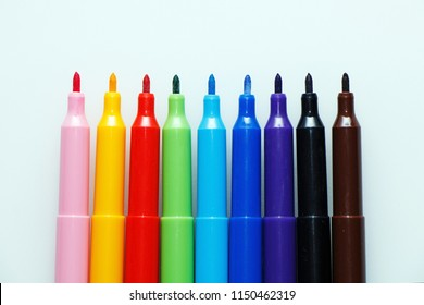 Multi-colored bright felt-tip pens on a white background