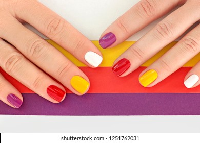 Multicolored bright saturated manicure on short nails close-up. Striped background. Nail art.
