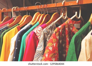 Multicolored bright women's dresses on hangers. Colorful wardrobe.