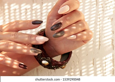 Multicolored brown milk manicure on oval long nails and a bracelet on his hand in the sun glare in the summer.
