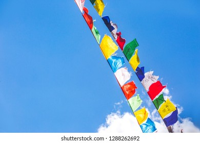 Multicolored Buddhist flags on a background of blue sky