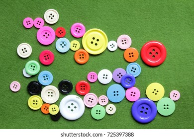 Multi-colored button,stud,buckle placed on the green background