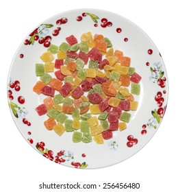 Multi-colored candied fruits on porcelain plate with an ornament in the form of berries, top view