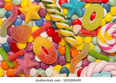 Multicolored candy and lollipops on a white background.