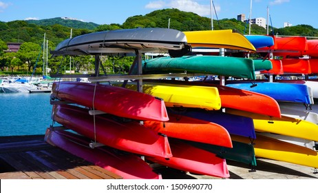 multi-colored canoes and kayaks on racks texture of colored kayaks on the background of the club's yachts on a sunny day.