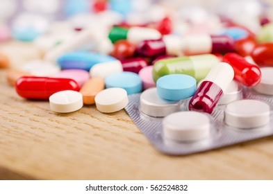 Multicolored Capsules and Pills Lying on a Wooden Surface. Closeup.