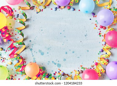 Multicolored carnival or birthday background on blue with a frame of colorful party balloons, streamers, confetti and candy around central copy space