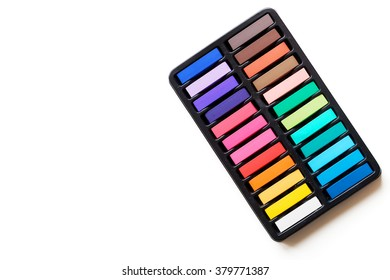 Multicolored chalks in the box over the white background