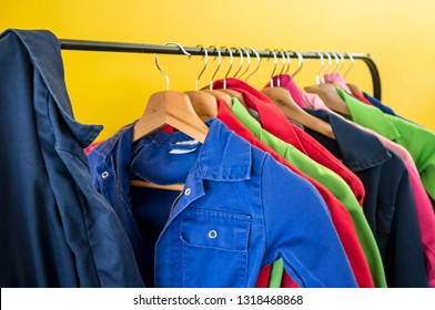 Multi-colored children's workwear for creative work hangs on hangers, against the backdrop of a bright yellow wall, in a kids club. Close-up.