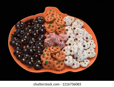 Multicolored chocolate covered pretzels as various Halloween critters with googly eyes on an orange pumpkin shaped plastic plate against a black background.