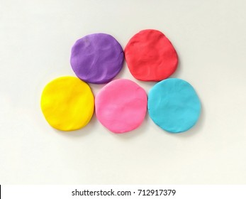 Multicolored circle shape are plasticine (clay) placed on a white background