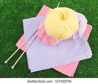Multicolored clews with napkins and needles on grass closeup