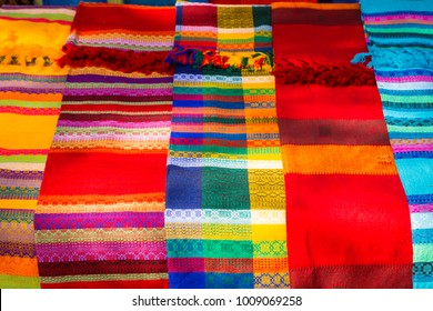 Multi-colored clothes. National clothes of Mexico. Multicolored textiles being representative for the latin america culture. Shawl of bright colorful. Souvenirs on the market at Chichen Itza.