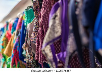 Multi-colored clothes, women's swimwear on hangers in the store.
