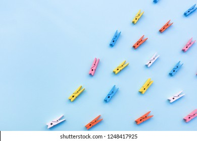 Multicolored clothespins on a blue background. Scattered clothespins in the right corner and free space for text.
