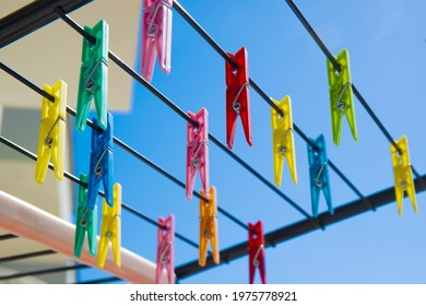 Multicolored clothespins on rope of blue sky background. Bright clothespins for drying clothes.