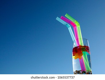 Multicolored cocktail straws and cooling stars in glass of water on blu sky background in sunny day. Summer drink concept. Selected focus