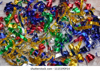 Multicolored confetti on a wooden background. Bright strips of colored foil. Colorful tinsel on holiday