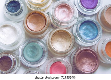Multicolored cream eyeshadows in jars on a marble background, close up