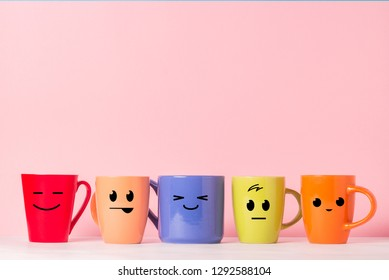 A lot of multicolored cups with funny faces on a pink background. The concept of a friendly company, a big family, meeting friends for a cup of tea or coffee, father's day, office, boss day.