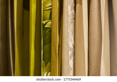 multi-colored curtains in the store. texture of multi-colored fabrics, closeup. samples of multi-colored fabric close-up. multi-colored fabric hanging in a store. Fabric colour and texture swatches.