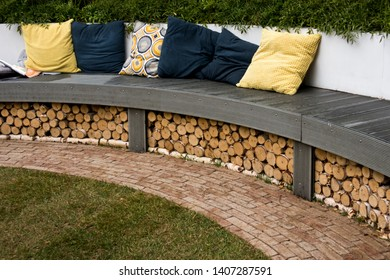 Multicolored cushions in the garden on long round bench of modern material.