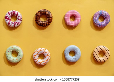 Multicolored donuts on a yellow background. Minimalism