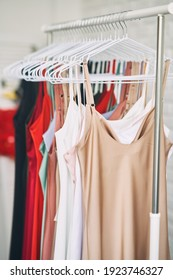 Multi-colored dresses hang on hangers in the store. Sale of women's dresses. Variety of different female colorful clothing hanging.