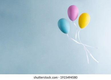 Multicolored easter eggs that look like balloons on a blue background, copy space. Easter card.