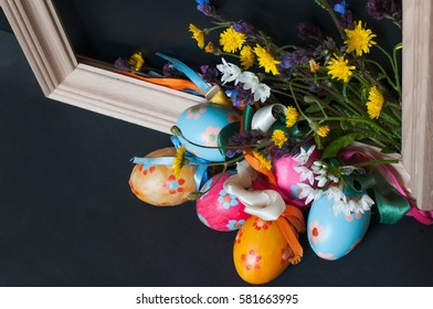 Multicolored Easter eggs in a wooden frame with a black background and spring flowers