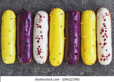 Multicolored eclairs with a taste of lemon, black currant, vanilla