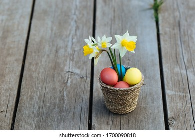 multicolored eggs in a wicker basket on a wooden background with flowers daffodils composition for Easter in April