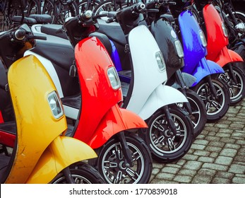 Multicolored electric mopeds stand in a row on paving stones
