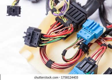 Multi-colored electrical wires with car connectors on a white isolated background during network repair by an engineer or mechanic in a service or workshop.