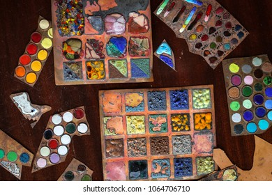 Multicolored enamel samples on metal, top view. The concept of creativity and design, the artist's studio, toning and soft focus.