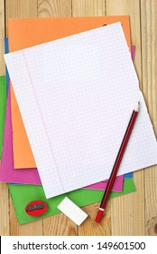 Multicolored exercise books, pencil, sharpener, eraser and clean sheet on table