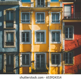 Multicolored facade of old traditional residential building in Lisbon, view of colorful frontage of living house in Portugal with multiple windows and balconies on bright sunny day
