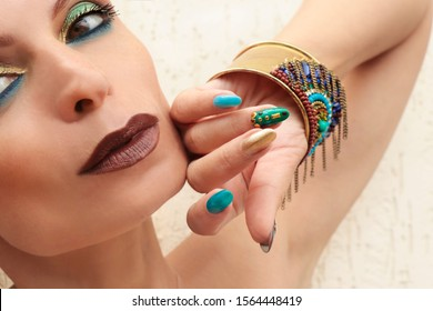 Multi-colored fashionable makeup and manicure in turquoise Golden blue and brown tones.Nail art with metal rhinestones on the nails.
